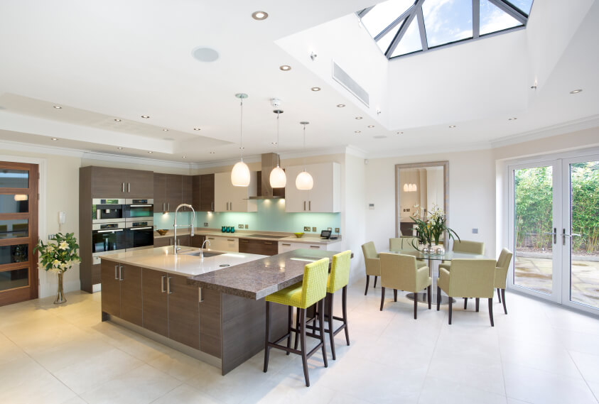 This gorgeous kitchen has hues of cool aqua and mint greens. The large skylight protrudes from the roof to bring in extra natural lighting to this space.