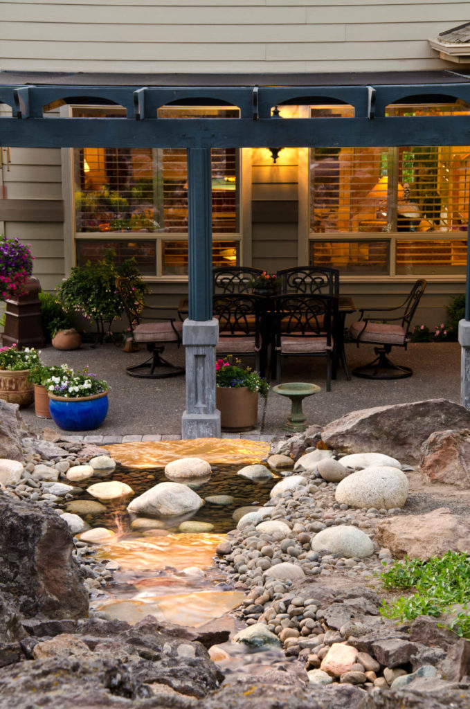 The view from behind the manmade waterfall shows the abundance of container gardens dotting the patio, for a colorful, eclectic aesthetic.