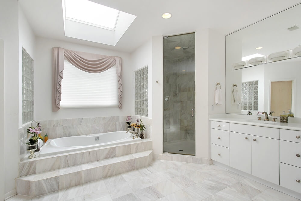 This light space features a tinted glass enclosed shower, a beautiful skylight, and sizable mirror allowing reflection of light and illusion of space. The simple white cabinetry complements the light stone tiles seen throughout the room, while a step leading into the relaxing spa bathtub offers convenience.