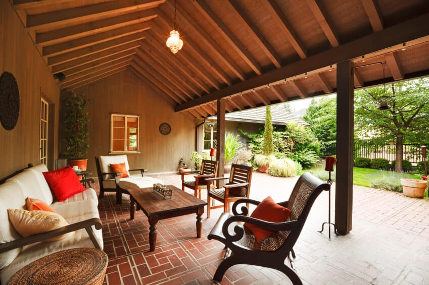 The wooden arch of this covered patio provides a sense of space and air to this narrow brick patio. From beneath the veranda, the brick patio continues out into the fenced-in backyard.