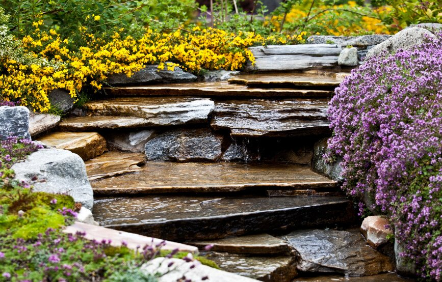 A garden waterfall surrounded by beautiful, colorful patches of flowers in purple and yellow. The shape of this winding stone waterfall resembles a series of steps.