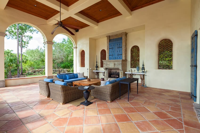 An enormous stone tile patio in a Spanish design, featuring latticed windows and an enormous stone fireplace. The bright blue of the seat cushions draw inspiration from the antique door displayed above the mantle.