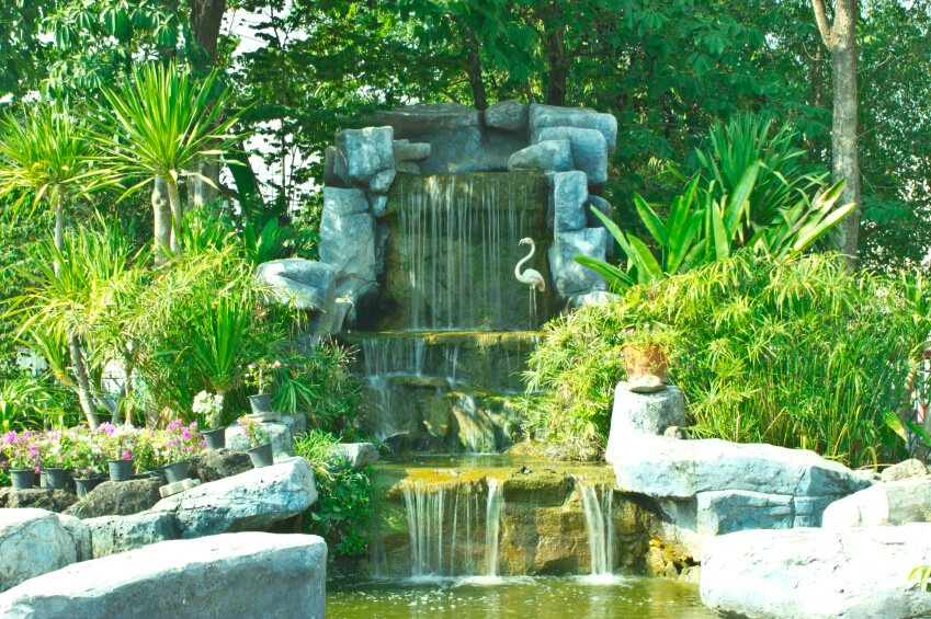 A large waterfall with a top reservoir and tropical plants around the edges. Flowers are kept in containers on the rocks for color. Near the tallest fall is a statue of a flamingo.