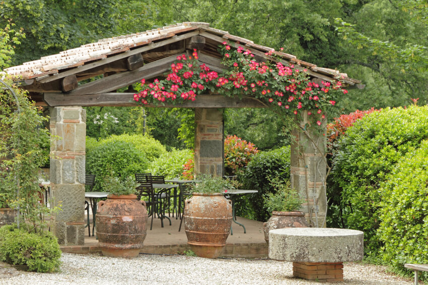 This aged patio sits beneath a wood and stone shelter. Antique terra cotta planters add greener to the front, while the other three sides are surrounded by tall shaped hedges.