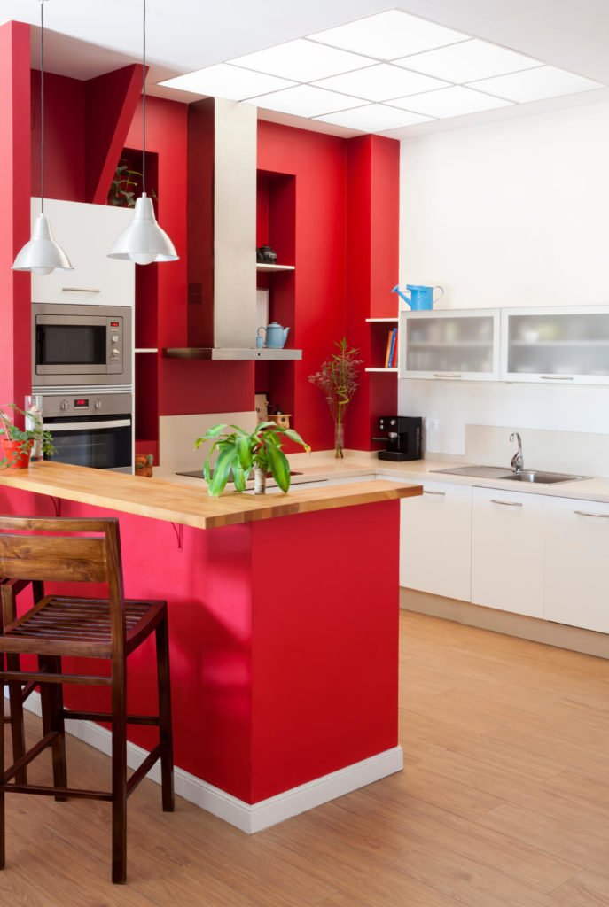 This kitchen is brightly lit and brightly colored, with red wall painting standing out in a mostly neutral palette. A grid-design skylight fills the room with sunlight at center.