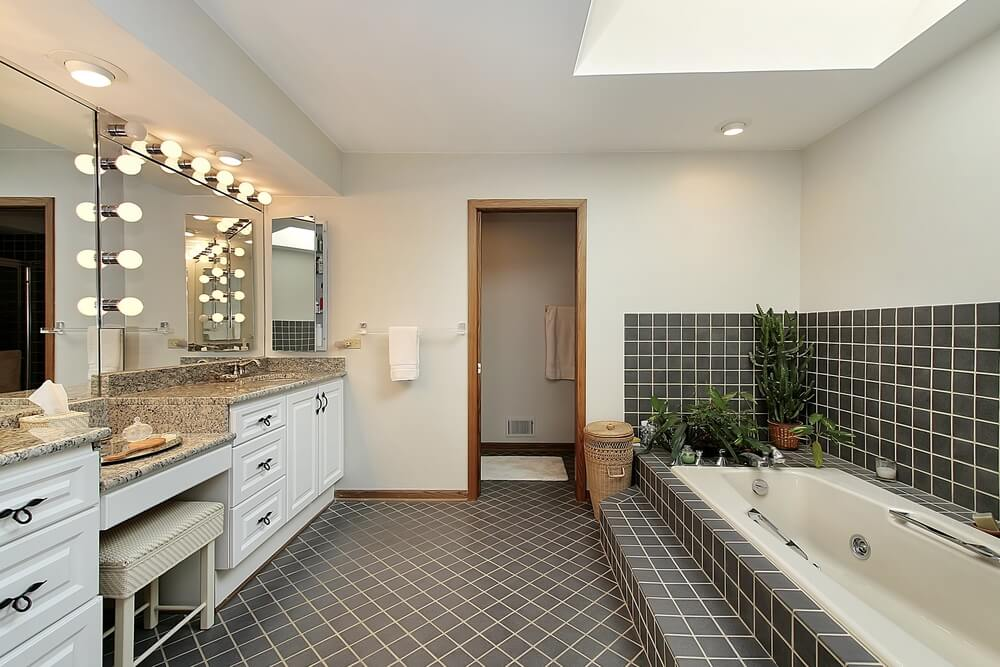 Black tiles with white grouting is attractive and eye catching in this wonderful bathroom space. The double vanity features a seating area, and soft lightbulbs offer the vintage ambiance of an old Hollywood dressing room. A skylight looms above the narrow tub, with decorative greenery strategically placed to provide beauty and additional texture.