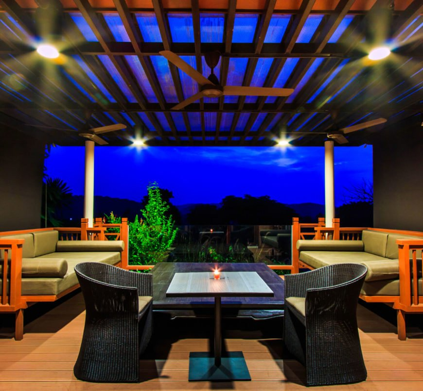 At night, this fabric-covered wooden shelter is the last bastion of light in the backyard. The combination of light wood sofas with black wicker dining chairs creates a sharp separation between the two functions of the seating arrangements.