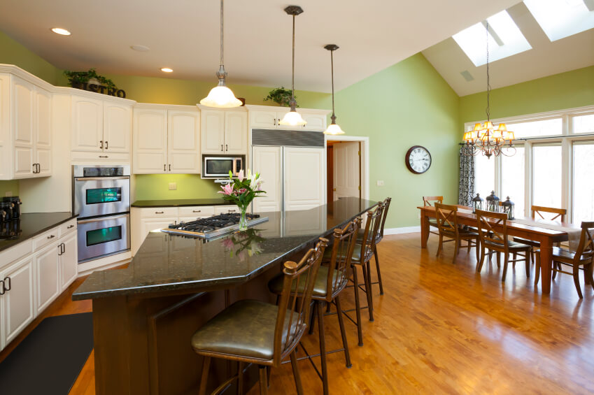 This kitchen features an expansive open-plan design, incorporating a large angular island and full dining space at right. The warm natural wood flooring and white cabinetry add contrast to the black countertops, all lit below wide skylights to the right.