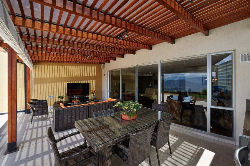 As light shines down on this pergola, it creates an eye-popping shadow pattern on the wicker dining set and living room seating arrangement. Uncommonly, a television and entertainment center is kept in this outdoor area. This is probably due to the large shades that can be drawn to enclose the space in case of inclement weather.