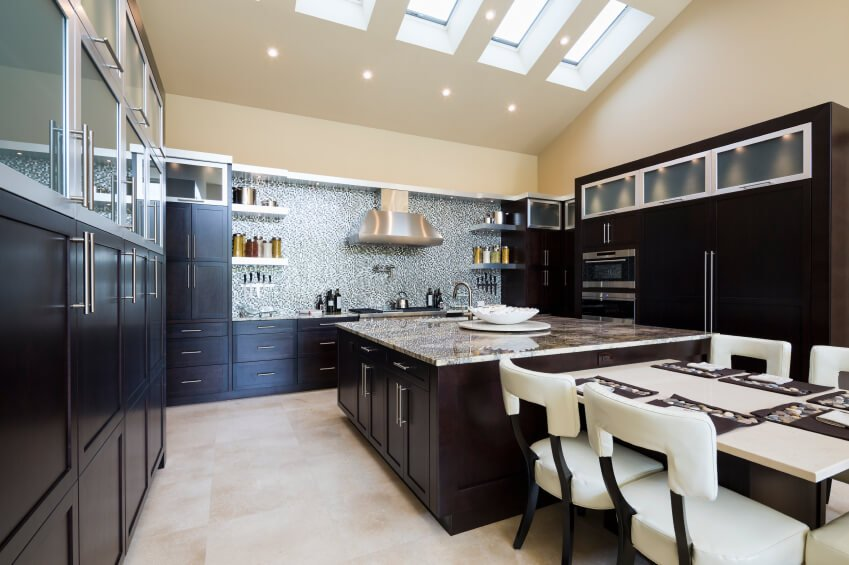 Here's another high contrast kitchen with dark wood cabinetry and light tile flooring. A massive island at center features abundant storage and countertop space, while the huge area is lit by a row of skylights in the vaulted ceiling.