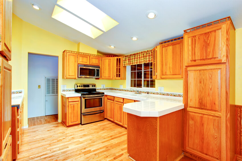 Under an angled ceiling, this bright, warm natural wood kitchen features white tile countertops and an expansive floor plan. A pair of deep set skylights add to the brightness.