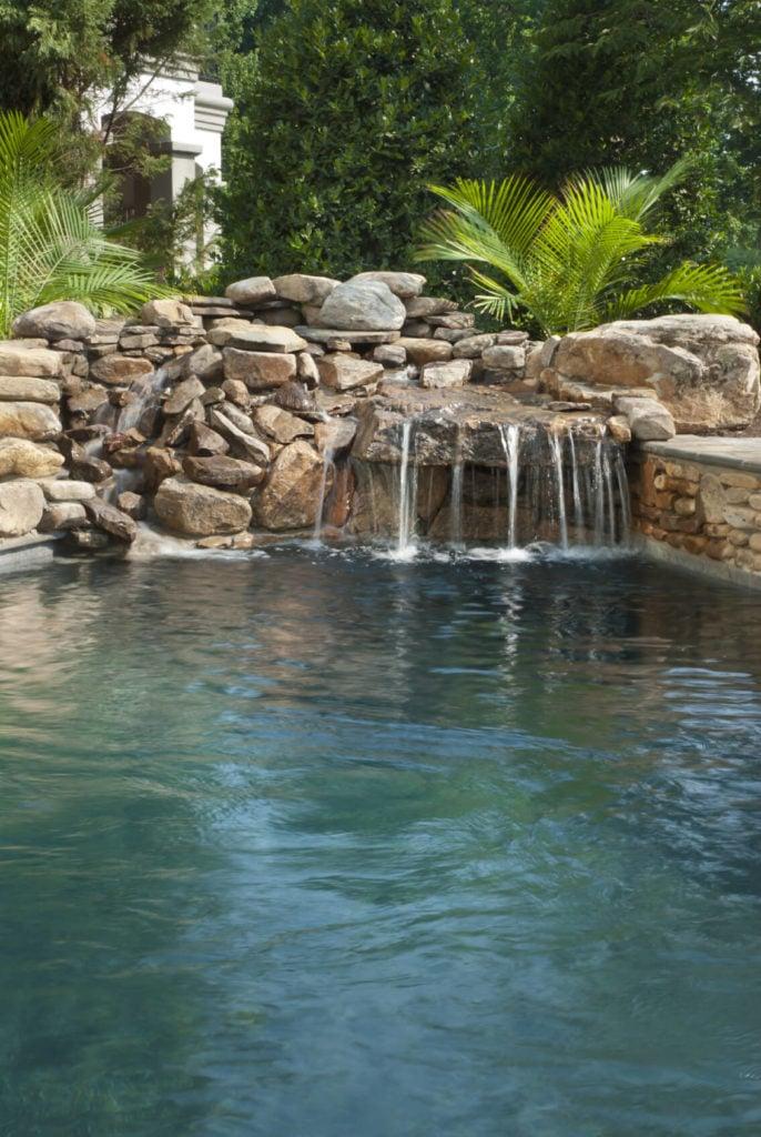 A layered stone waterfall with lush foliage behind it.