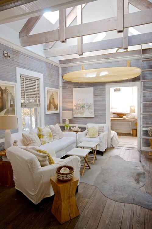 This fun little living room has a great summer feel. With gray wooden panels on the wall and ceiling, this quaint space is wild and pleasant. Beautiful light filtering down from the skylights to give it the perfect open and delightful atmosphere.