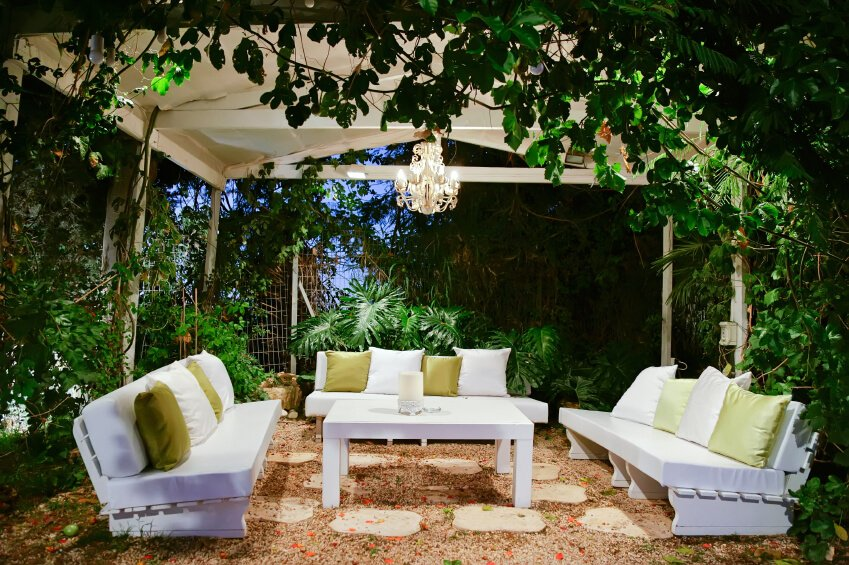 This gorgeous, serene garden patio rests beneath an iron structure. Simple white benches are covered with white cushions and green accent pillows. A small chandelier adds an incredibly elegant touch.