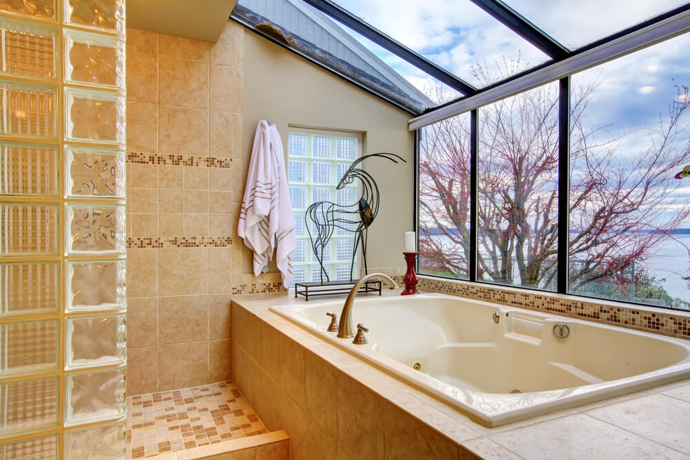 This luxurious bathroom space has a three seasons room feel, with gorgeous views of nature and a large, peaceful lake. The delicate tile-work offers interest in pattern and details, with darker tiles interspersed amongst the lighter pieces.