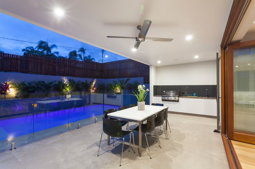 A glass balustrade separates this covered stone patio and outdoor kitchen from the rest of the backyard, including the pool. A single ceiling fan keeps the air circulating in this mostly closed-off patio.
