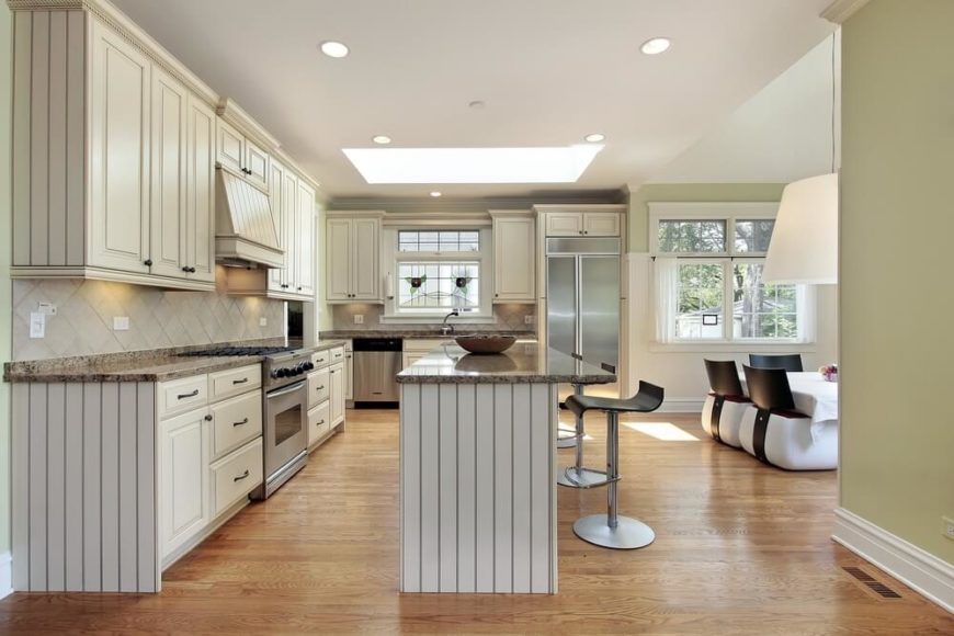This contemporary kitchen sees its light hardwood floor and lengthy granite countertops glowing under the light of a large square skylight set in the center of the room. The open-plan space incorporates a dining room, at right.