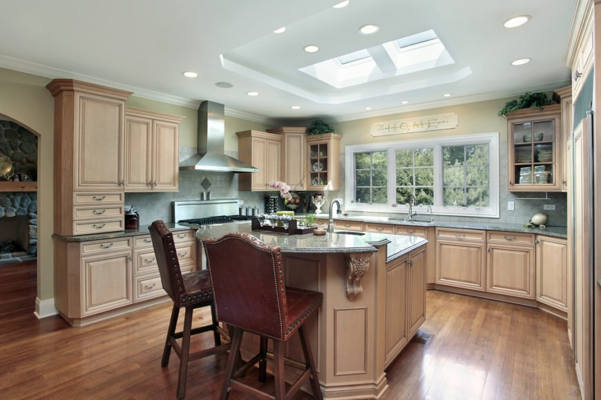 This luxuriously appointed, traditionally styled kitchen centers around a large two-tiered island, lit via series of recessed lights and a dual-pane skylight. With sleek natural hardwood flooring and light cabinetry, the room positively glows.