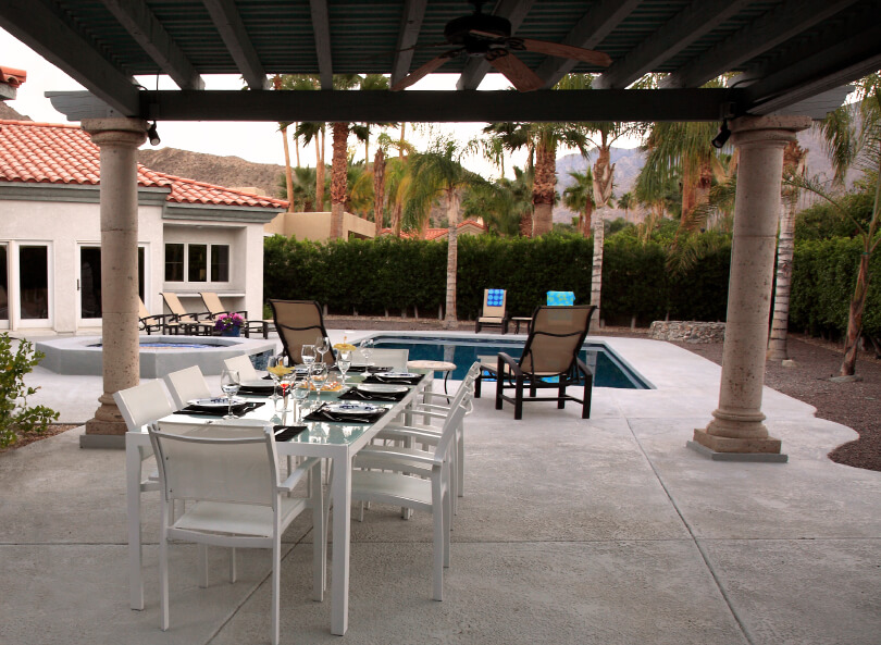 The entrance to this beautiful concrete pool complex is from beneath a covered patio. An outdoor eating area in white is secluded beneath the roof, which includes ceiling fans to keep the air circulating for a comfortable dining experience.