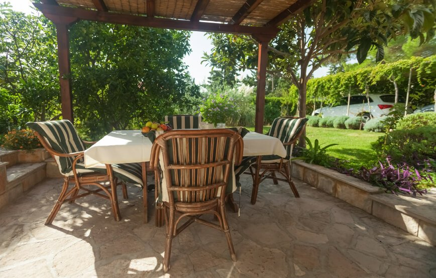 A pergola covered with natural fiber matting provides shade over this sunken stone patio. Green and white striped chair cushions pull color in from the thickly foliaged yard. The driveway sits between hedges and a row of shade trees.