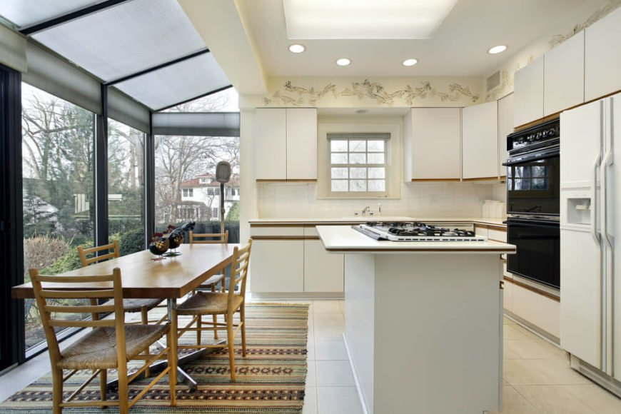 In a kitchen already well-lit by a wraparound set of glazing, creating a sort of greenhouse effect, a large central skylight adds to the bright buoyancy of the space. The cozy layout includes a large island with built-in range and natural wood dining table.
