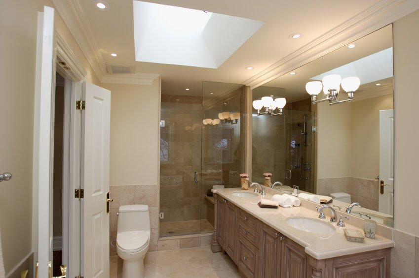 Mirror sconces, recessed lighting, and a skylight work together to highlight this lovely bathroom space. A toilet is positioned precariously close to the door, and a glass enclosed shower beckons use. A creamy porcelain topped double vanity takes up residence, offering plenty of space for daily preparations.