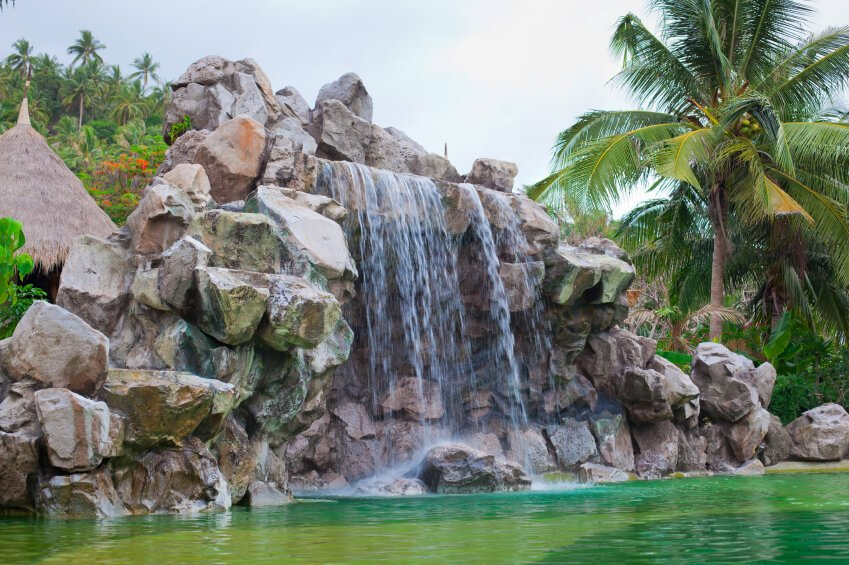 A rocky swimming pool waterfall surrounded by palm trees and a palm-roof shelter.