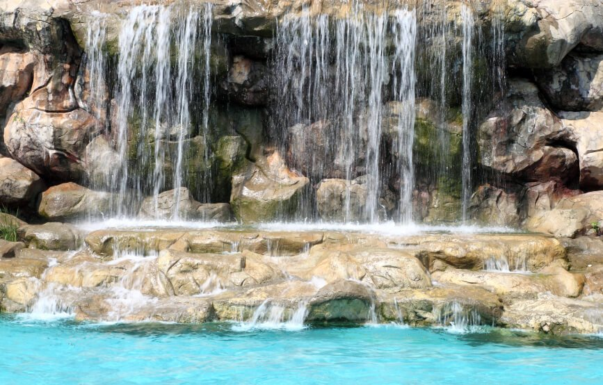 A large artificial waterfall pounding down on a stone platform and then trickling down into the main pool.