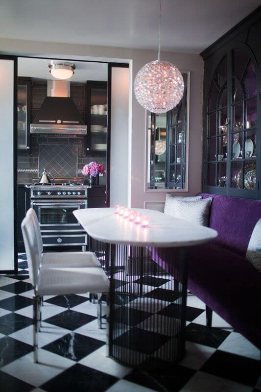 A stunning dining room with a velvet bench seat on one end against the built-in china cabinets and two white vinyl dining chairs. The checkerboard tile floor continues into the kitchen through the archway.