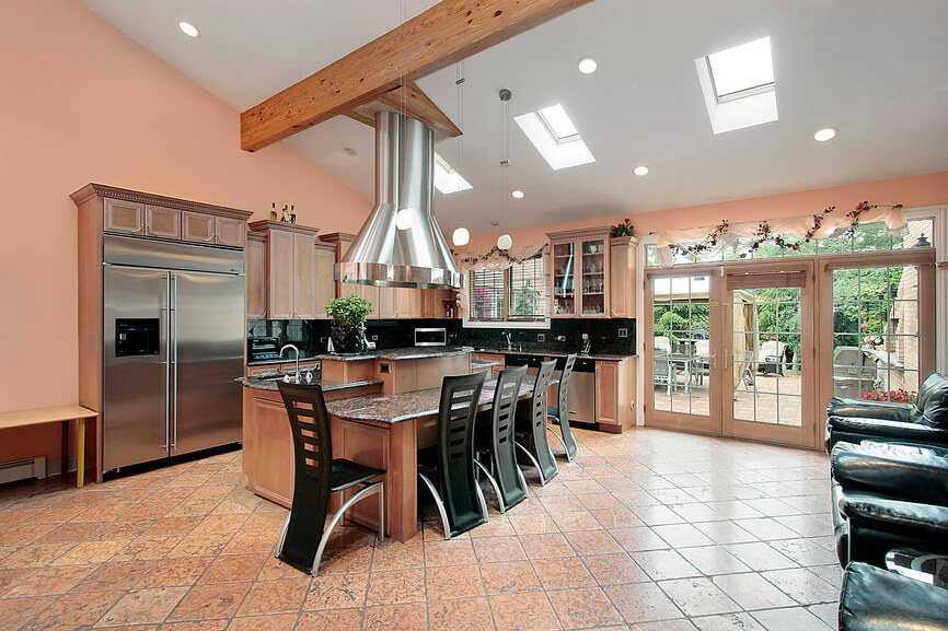 This modern kitchen has a unique set of curved chairs and an attractive layout of tiled flooring. Skylights line the angled ceiling to pull light directly into the main section of the space.