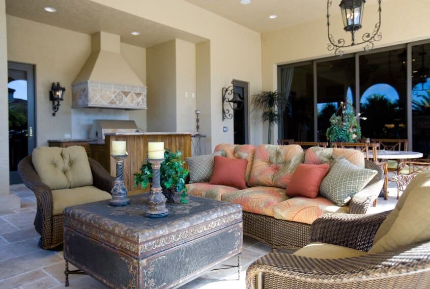 A wicker patio set with an aged antique chest serving as a coffee table take center stage in on this covered southwestern style patio. Tinted windows to the interior give this space a sense of intimacy and privacy, even from the rest of the home or family.