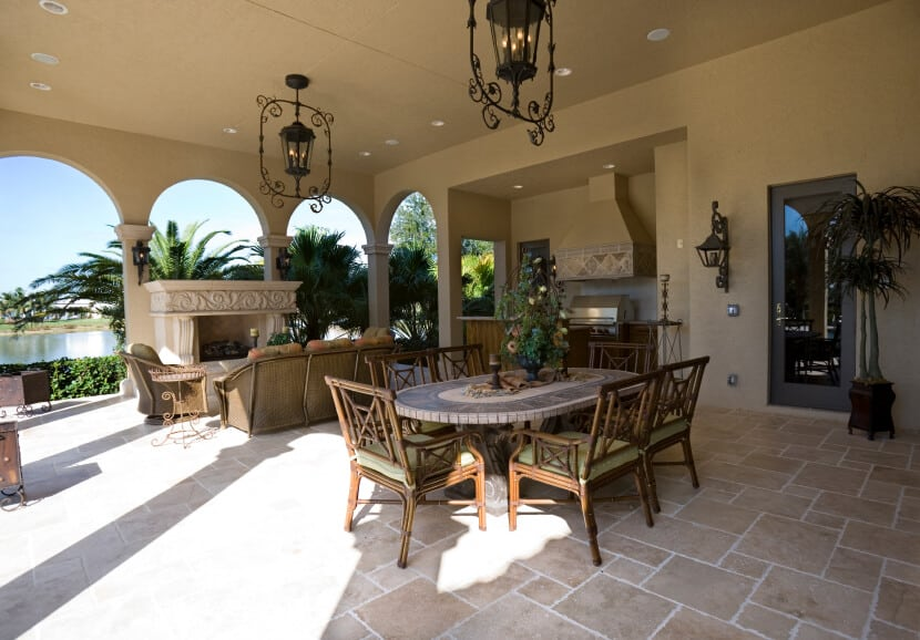 This incredibly spacious covered patio features a small outdoor kitchen, a large formal dining table and a cozy wicker seating area in front of a massive plaster and stone fireplace. Through the series of elegant archways we can see the waterfront and a collection of tropical palms swaying in the breeze. Wrought iron pendant lighting along with a few pot lights keep this space well lit into the night.