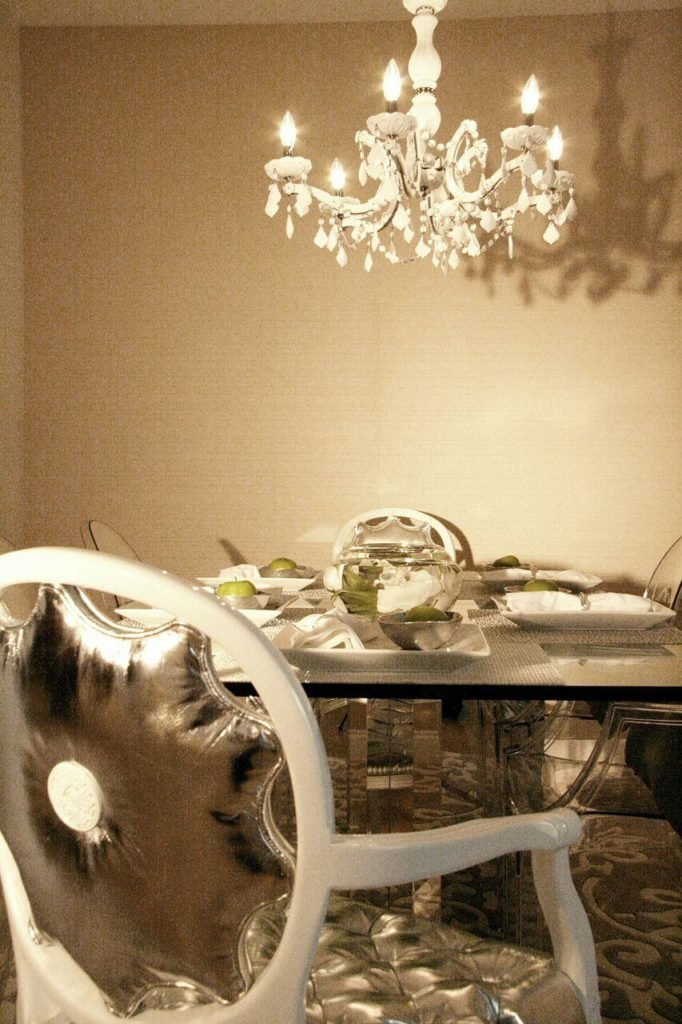 A close up of the dining table, showing the chrome supports of the table and the glass top. The dining chairs are upholstered in a shiny metallic silver fabric.