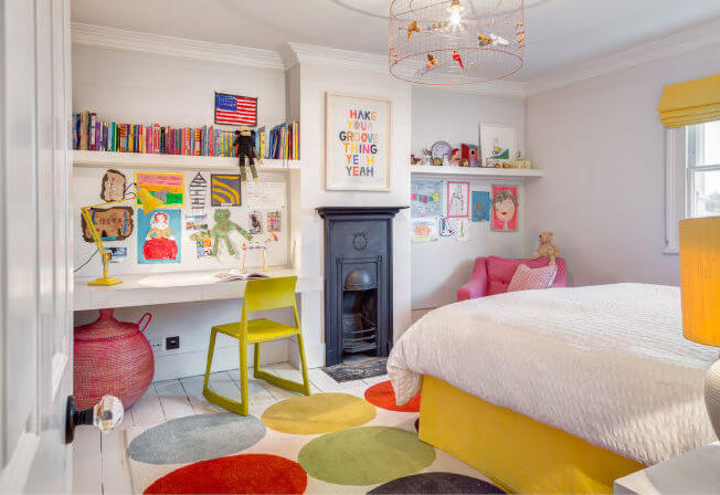 A child's room with a built-in desk and the narrow, original fireplace intact. The light fixture is unique, made to look like a songbird cage.