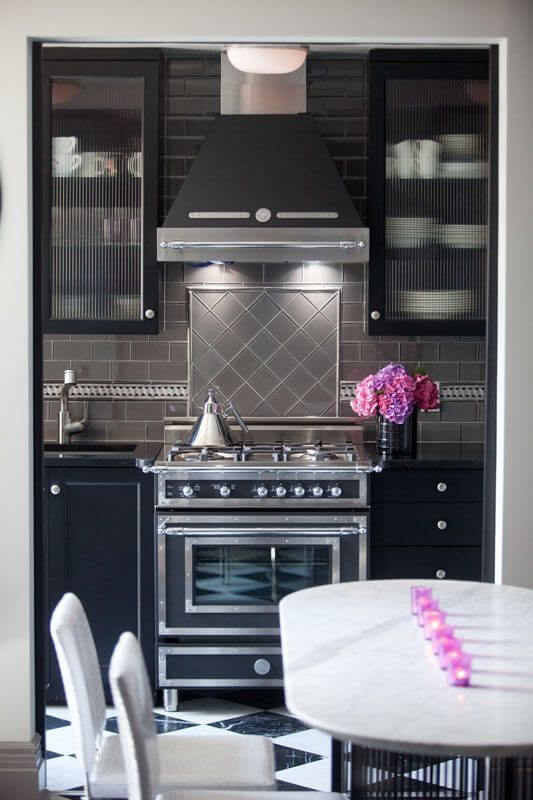 Through the archway is the kitchen with an oven in a vintage style. The backsplash is a charcoal subway tile with a mosaic above the stovetop. The archway hides frosted-glass pocket doors that can be closed to separate the two spaces for a more intimate atmosphere.