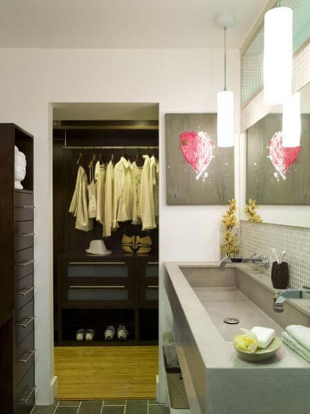The trough sink has two faucets. The archway leads into the walk-in closet for the primary suite. On the opposite side of the sink is towel storage and a line of drawers.