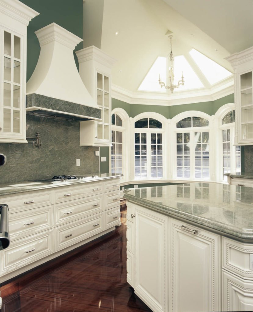 This kitchen has a bold grey-green marble on the backsplash and countertops. Angled skylights in the geometrical addition move light into this elegant room.