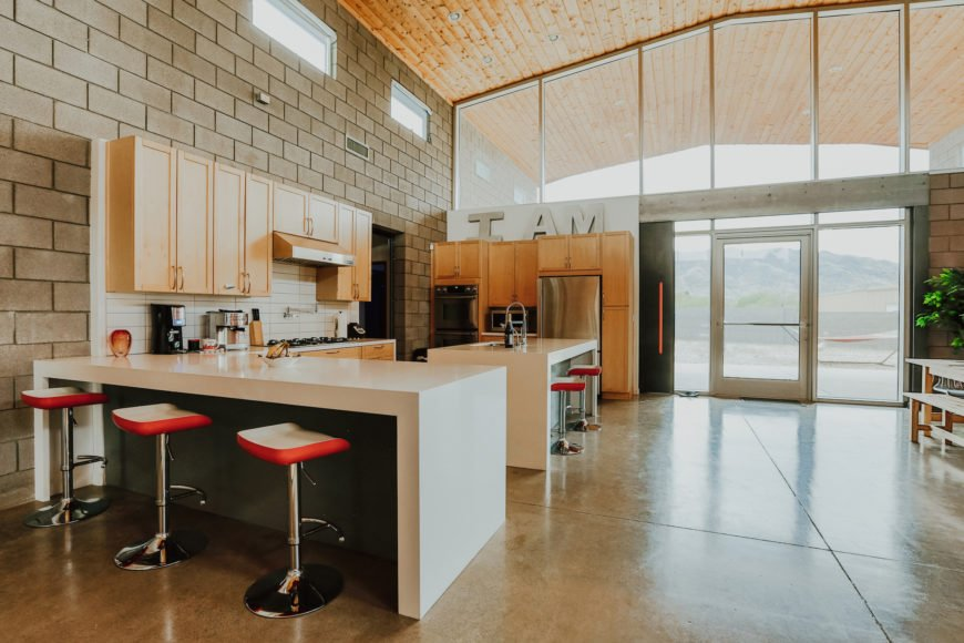 Both large counters feature space for dining, with a set of red and white cushioned, chrome bar stools. The timber-lined roof can be clearly seen extending outward here.