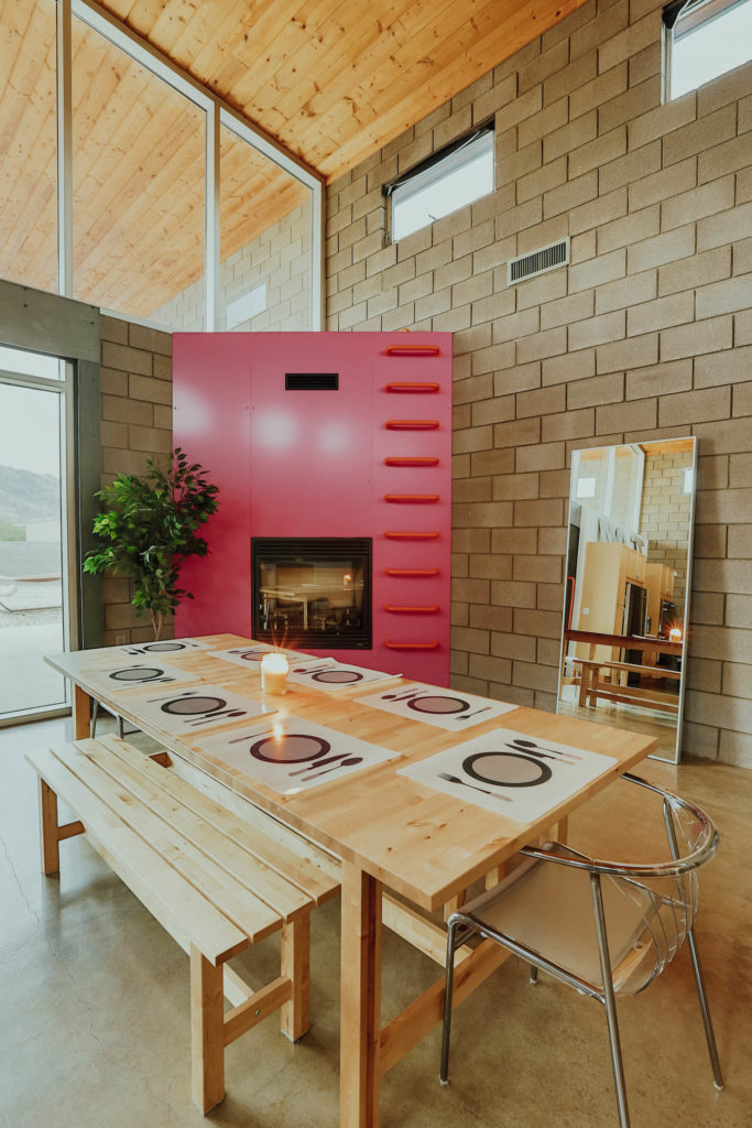 The bright natural wood dining table features matching bench seating and modern chrome chairs on the ends. The unique pink fireplace structure features a ladder for access to expansive views.