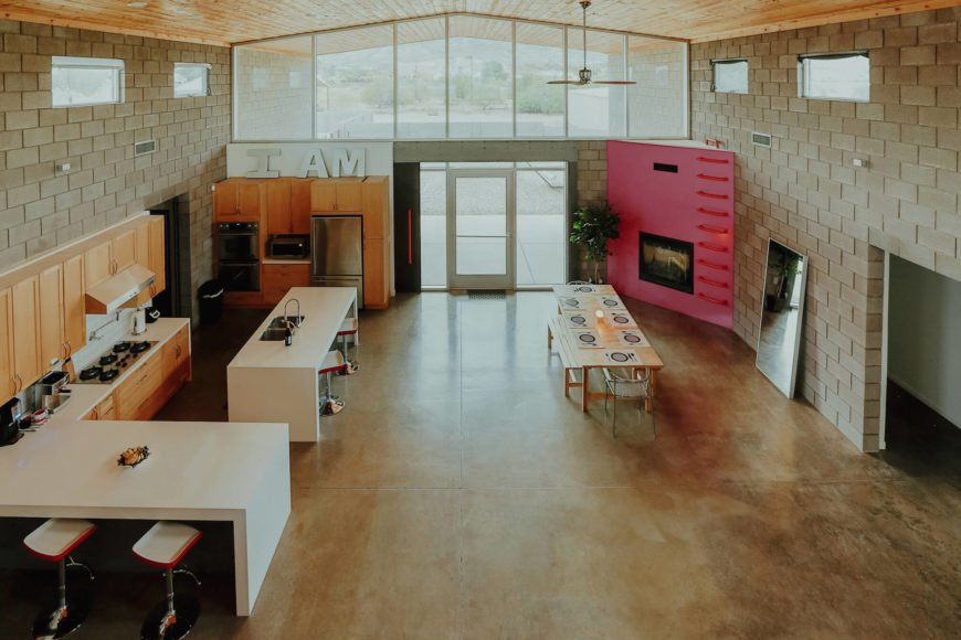 Viewed from above, the front half of the home is a spare, open expanse spiked with unique details, including the wood dining table and pink fireplace structure sunlit via an expanse of large windows.