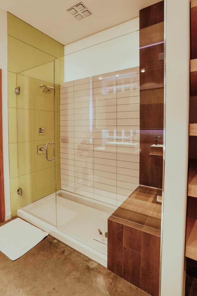 The glass-enclosed walk-in shower holds a trio of textural details: rich natural wood, white brick tiles, and large format yellow tile.