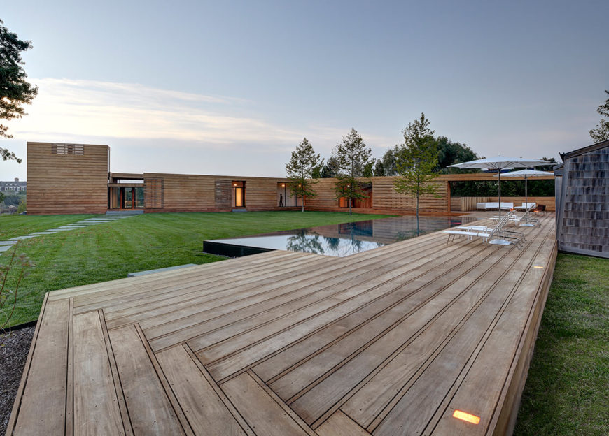 This wide shot reveals the extensive boardwalk wrapping the entire structure, unifying the pool house, massive patio, and home itself.