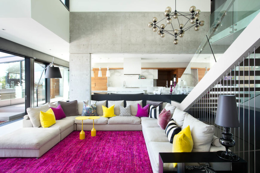 This open concept living room features a burst of color amidst the neutral structural tones. Behind the wraparound sectional we see the open kitchen and dining spaces.