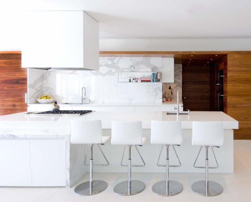 Viewed head on, the kitchen makes perfect contrast between bold white surfaces and rich cedar paneling. The large island features a built-in sink and range plus dining space for four.
