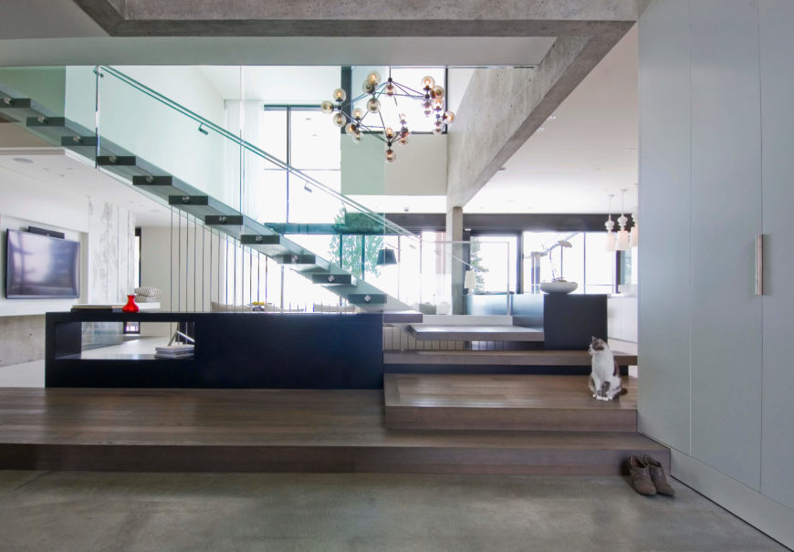 Moving back to view the entire open plan, double-height living space, we see the intricate mixture of glass, steel, hardwoods, concrete, and marble that provide a lived in touch to the ultra-modern home.