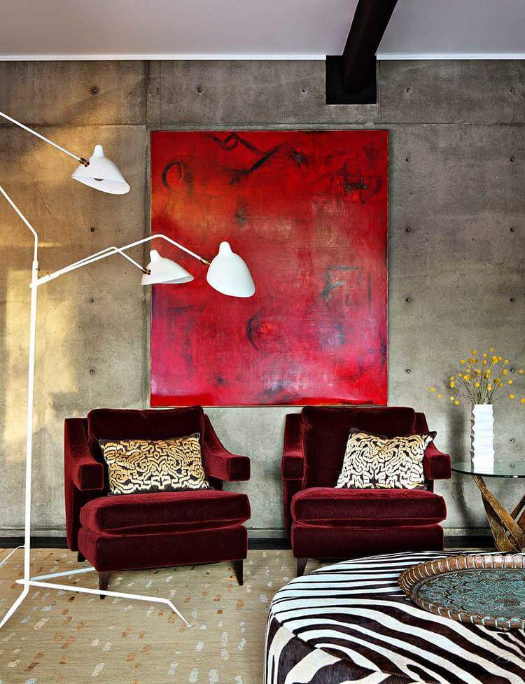 Bursts of color appear throughout, including this pair of lush red chairs beneath a bright red painting, against the concrete structural wall. A large zebra print ottoman stands at right.