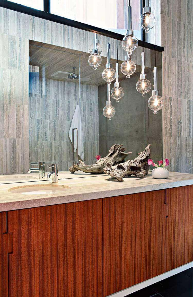 A focused shot at this mid-century primary bathroom's sink counter with a very attractive decoration along with classy pendant lights.