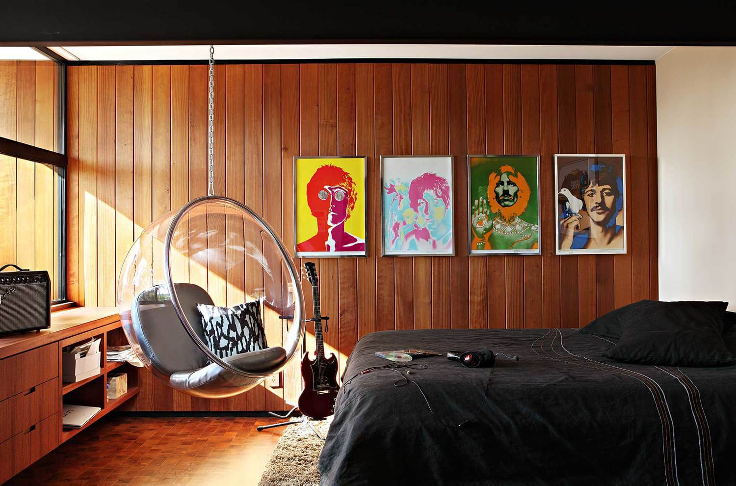 A mid-century modern primary bedroom featuring a very attractive hanging chair and a stylish black bed surrounded by rustic walls.