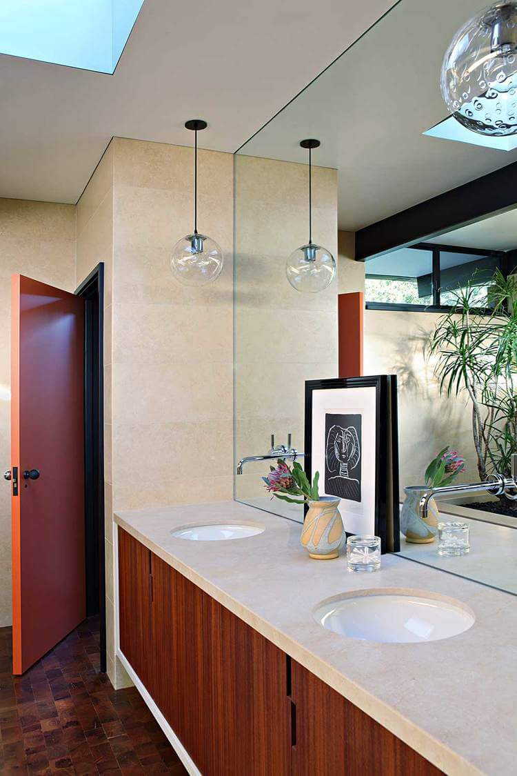A primary bathroom in mid-century style featuring a double sink lighted by pendant lights.