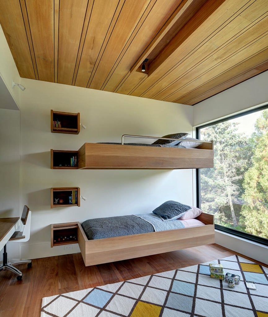 A kids' bedroom features floating wall-mounted bunk beds in natural wood, plus a built-in desk and bookshelves. Another large format window opens this room to natural light.